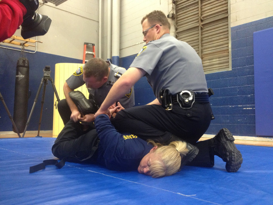 Photo - Oklahoma City police demonstrate the proper procedure for using a hobble restraint system. Belts are used to restrict the movement of a person's legs. An officer turned her head  to the side as the restraints were applied.