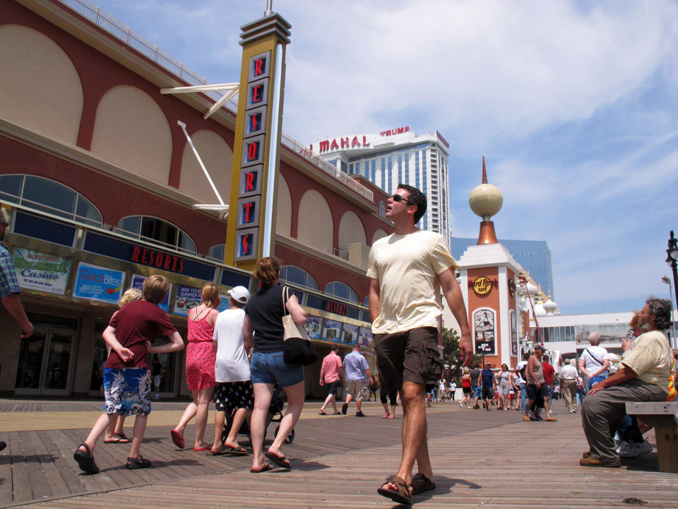 Photo - FILE - In this June 27, 2013 file photo, pedestrians walk on the Atlantic City N.J. Boardwalk with the Resorts, Trump Taj Mahal and Revel casinos in the background. The rapid disintegration of Atlantic City's casino market might be an early indicator of what could happen in other parts of the country that have too many casinos and not enough gamblers. (AP Photo/Wayne Parry, File)