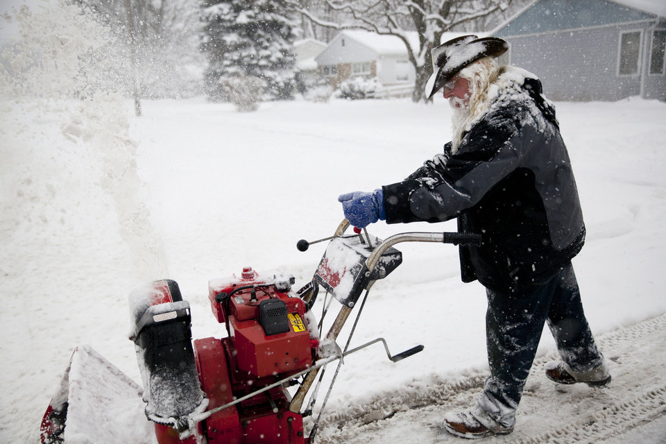 Photo - Lee Tuttle, 66, blows snow off of his driveway on Sunday, Jan. 5, 2014 at his home on Miller Road in Flint, Mich. Michigan residents have been preparing for the harshest winter conditions in 20 years.(AP Photo/The Flint Journal, Michelle Tessier) LOCAL TV OUT; LOCAL INTERNET OUT
