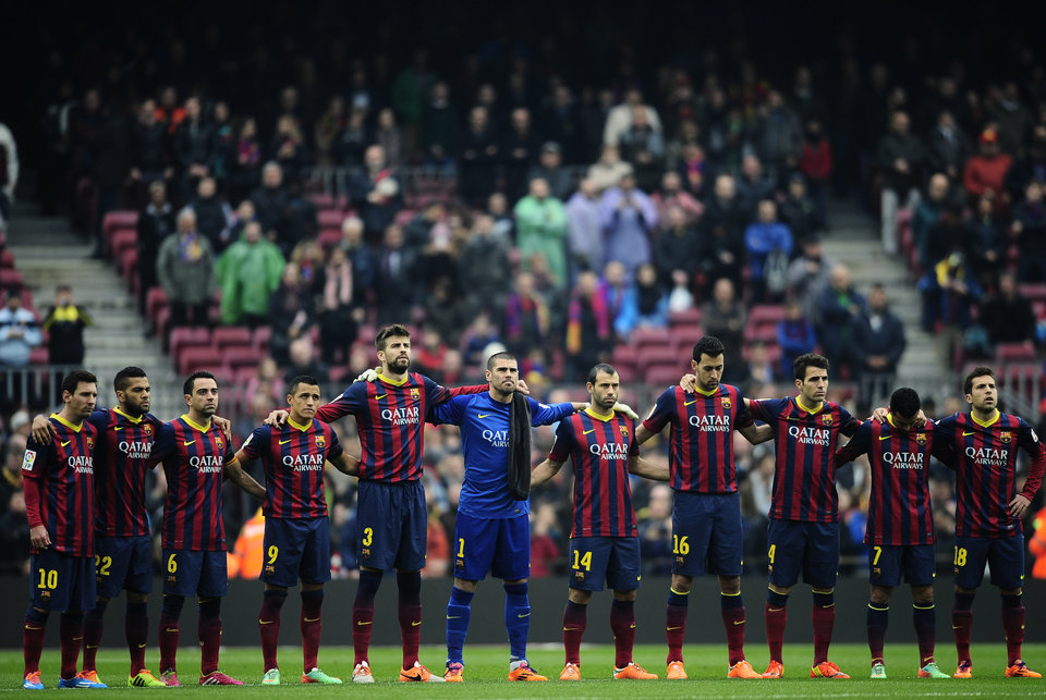 Photo - FC Barcelona's players observe a minute of silence in memory of Luis Aragones prior to Spanish La Liga soccer match between FC Barcelona and Valencia at the Camp Nou stadium in Barcelona, Spain, Saturday, Feb. 1, 2014. Former footballer and manager of Spain national team Luis Aragones died Saturday at the age of 75. (AP Photo/Manu Fernandez)