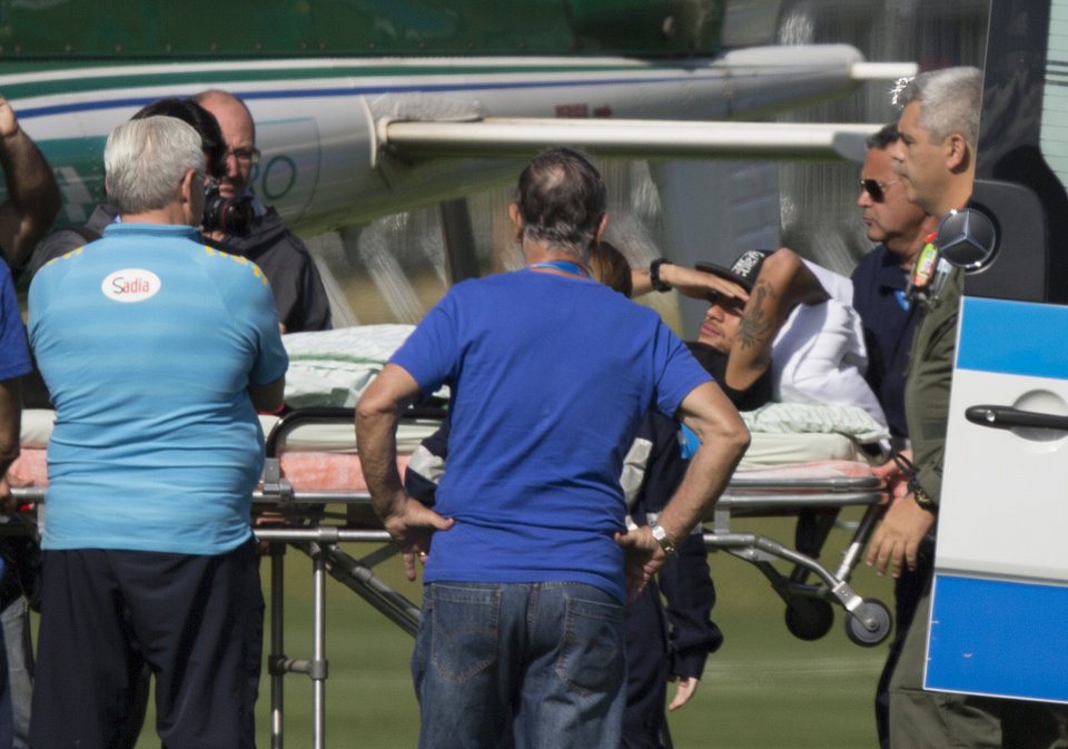 Photo - Brazil's Neymar is carried on a a stretcher to a medical helicopter at the Granja Comary training center, in Teresopolis, Brazil, Saturday, July 5, 2014. Neymar was airlifted from Brazil's training camp Saturday and will be treated at home for his back injury. Neymar, the biggest football star in Brazil, was ruled out of the rest of the World Cup after fracturing his third vertebra during Friday's 2-1 quarterfinal win over Colombia. (AP Photo/Leo Correa)