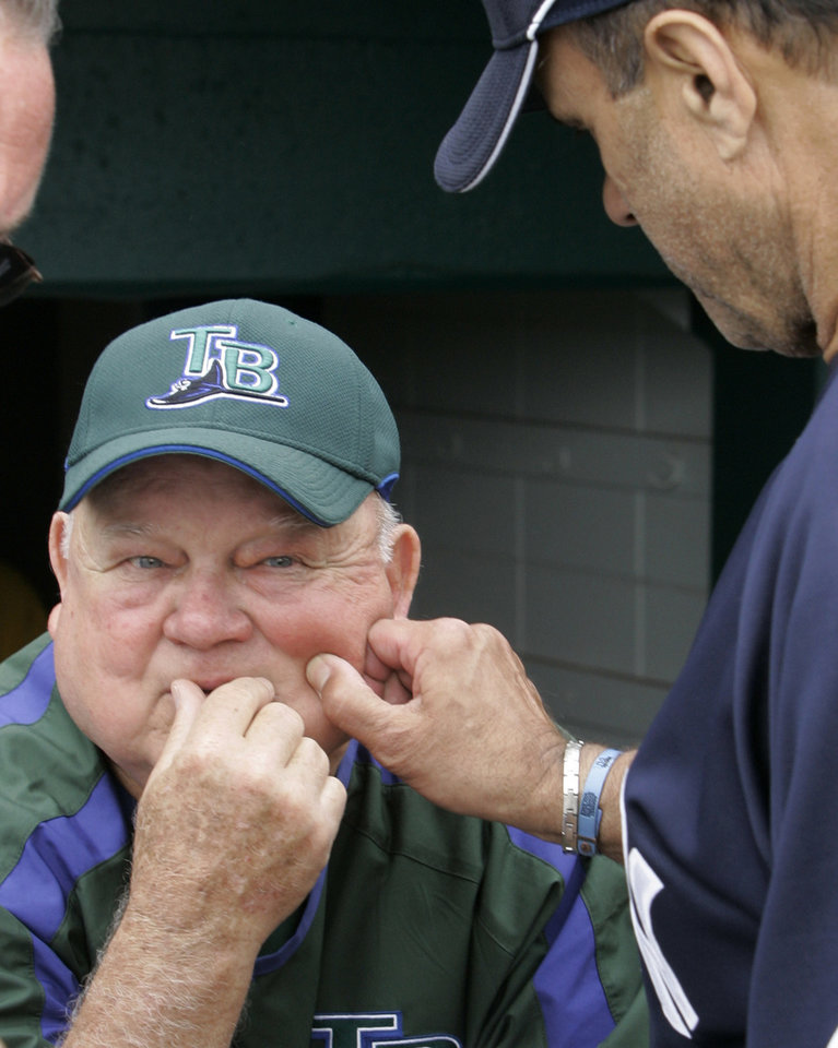 Photo - FILE - In this March 2, 2007, file photo, Tampa Bay Devil Rays senior adviser Don Zimmer, left, has his cheek pinched by New York Yankees manager Joe Torre prior to a spring training baseball game in St. Petersburg, Fla. Zimmer, a popular fixture in professional baseball for 66 years as a manager, player, coach and executive, has died. He was 83. Zimmer was still working for the Rays as a senior adviser. The team confirmed Wednesday night, June 4, 2014, that he had died. Zimmer had been in a rehabilitation center in Florida since having heart surgery in mid-April. (AP Photo/Al Behrman, File)