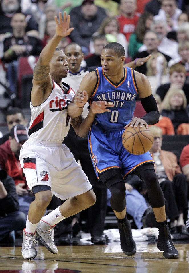 Photo - Oklahoma City Thunder guard Russell Westbrook, right, drives on Portland Trail Blazers guard Damian Lillard during the second half of an NBA basketball game in Portland, Ore., Friday, April 12, 2013.  Westbrook scored 33 points as the Thunder won 106-90. (AP Photo/Don Ryan) ORG XMIT: ORDR109