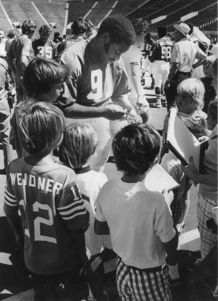 Dewey Selmon signs autographs in this undated photograph. Selmon was inducted into the Oklahoma Sports Hall of Fame on March 20, 2012.
