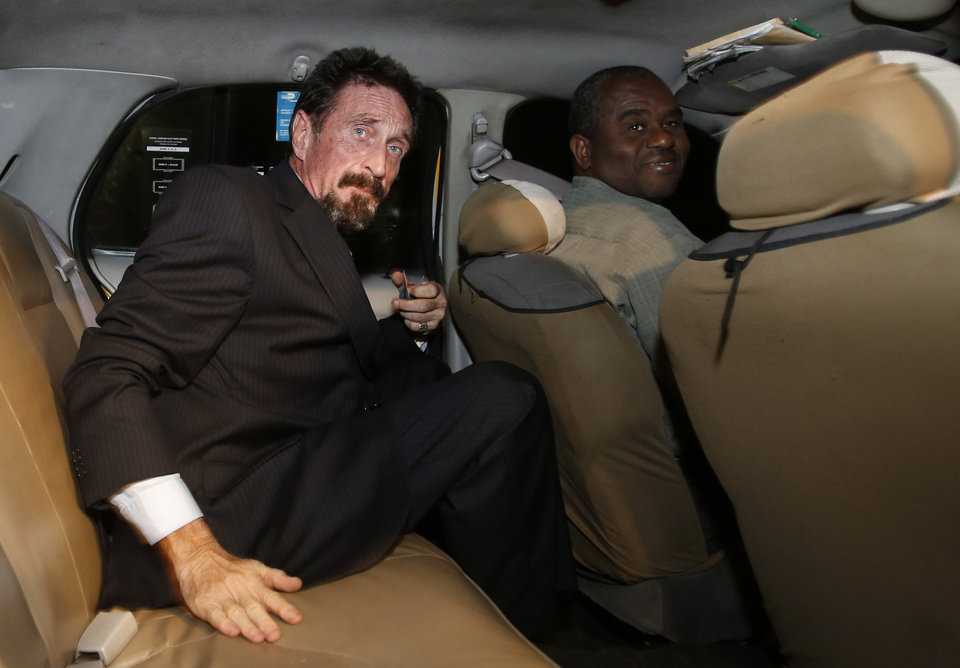 Anti-virus software founder John McAfee, left,  sits in a taxi cab in the South Beach area of Miami Beach, Fla., on his way to dinner Wednesday, Dec 12, 2012. McAfee arrived in the U.S. on Wednesday night after being deported from Guatemala, where he had sought refuge to evade police questioning in the killing of a man in neighboring Belize. (AP Photo/Alan Diaz)