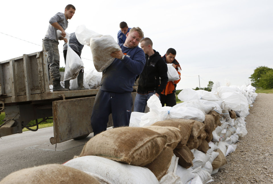Photo - Bosnian people place sandbags onto road to protect the city from flooding near Orasje 200 kms north of Sarajevo, on Sunday May 18, 2014. Packed into buses, boats and helicopters, carrying nothing but a handful of belongings, tens of thousands fled their homes in Bosnia and Serbia, seeking to escape the worst flooding in a century. (AP Photo/Amel Emric)