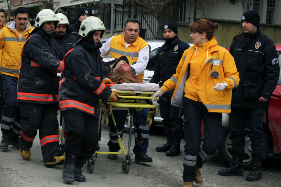 Photo - Medics carry an injured woman on a stretcher to an ambulance after a suspected suicide bomber detonated an explosive device at the entrance of the U.S. Embassy in the Turkish capital, Ankara, Turkey, Friday Feb. 1, 2013. The bomb appeared to have exploded inside the security checkpoint at the entrance of the visa section of the embassy. A police official said at least two people are dead. (AP Photo/Burhan Ozbilici)