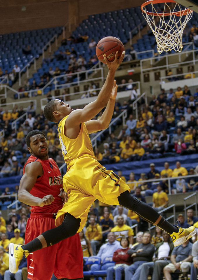 West Virginia's Gary Browne, right, scores ahead of Radford's Ya Ya Anderson, left, during the second half of an NCAA college basketball game at WVU Coliseum in Morgantown, W.Va., Saturday, Dec. 22, 2012. West Virginia defeated Radford 72-62. (AP Photo/David Smith)
