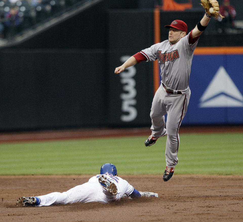Arizona Diamondbacks second baseman Aaron Hill leaps for the ball thrown by catcher Henry Blanco as New York Mets\' Andres Torres steals second base during the third inning of a baseball game Saturday, May 5, 2012, in New York. (AP Photo/Frank Franklin II)
