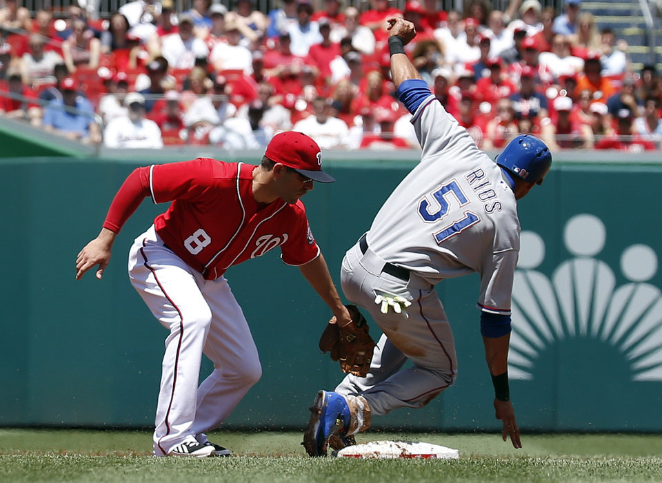 Photo - Washington Nationals second baseman Danny Espinosa (8) tries to tag Texas Rangers' Alex Rios (51) on a steal-attempt during the first inning of a baseball game at Nationals Park, Sunday, June 1, 2014, in Washington. Rios was ruled out on the play. (AP Photo/Alex Brandon)