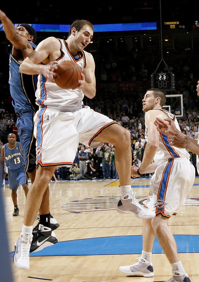 Oklahoma City's Nenad Krstic grabs a rebound in the final seconds of the game between Dominic McGuire, left of Washington, and Nick Collison during the NBA basketball game between the Oklahoma City Thunder and the Washington Wizards at the Ford Center in Oklahoma City, Wed., March 4, 2009. PHOTO BY BRYAN TERRY, THE OKLAHOMAN