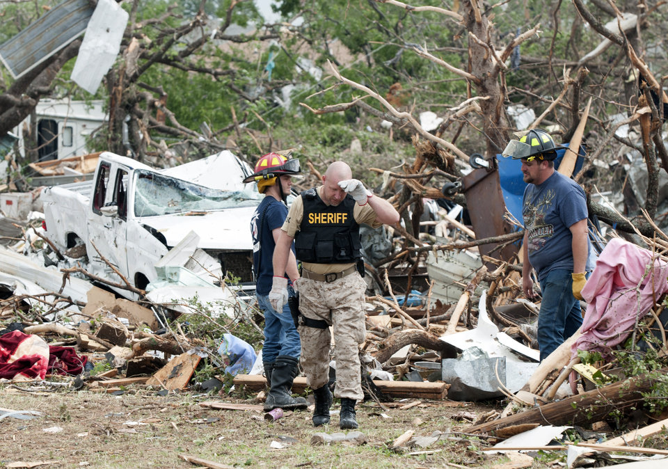 Photo - Emergency personnel look through debris on near Granbury, Texas  on Thursday, May 16, 2013. Ten tornadoes touched down in several small communities in Texas overnight, leaving at least six people dead, dozens injured and hundreds homeless. Emergency responders were still searching for missing people Thursday afternoon. (AP Photo/Rex C. Curry)
