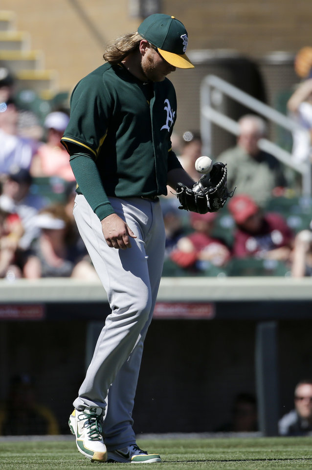 Photo - Oakland Athletics starting pitcher A.J. Griffin walks back to the mount after giving up the third run against the Colorado Rockies during the first  inning of a spring training baseball game in Scottsdale, Ariz., Saturday, March 8, 2014. (AP Photo/Chris Carlson)