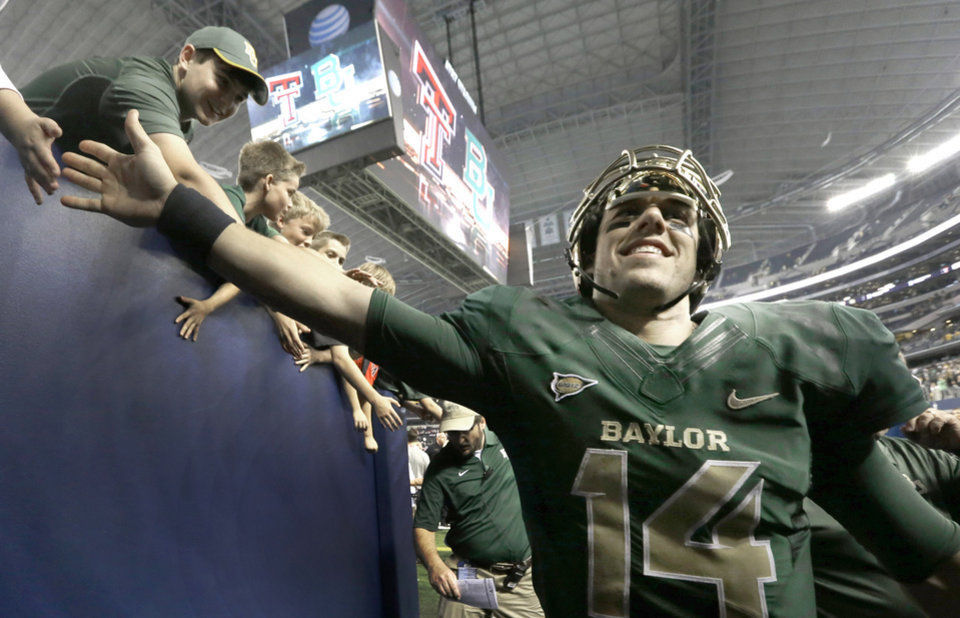 Photo - Baylor quarterback Bryce Petty walks off the field smiling after an NCAA college football game against Texas Tech in Arlington, Texas,  Saturday, Nov. 16, 2013. Baylor won 63-38.  (AP Photo/LM Otero)