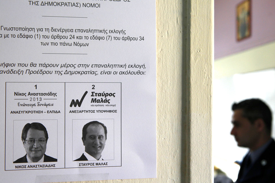 Photo - A replica of a ballot with two presidential candidates, right-wing opposition leader Nicos Anasatsiades, left, and left-wng Stavros Mallas is posted on a wall by a police officer, right, at a polling station in southern port city of Limassol, Cyprus, Sunday, Feb. 24, 2013. Opposition party leader Nicos Anastasiades garnered 45.46 per cent of the vote in the first round of voting, some 18 points over communist-backed Stavros Malas. (AP Photo/Petros Karadjias)