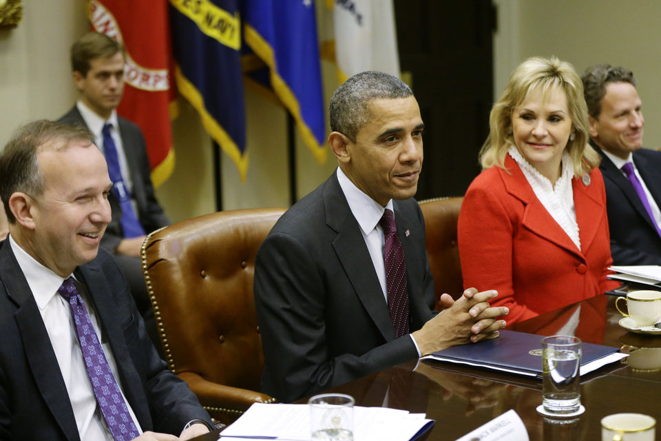 Photo - President Barack Obama, flanked by National Governors Association (NGA) Chairman, Delaware Gov. Jack Markell, and NGA Vice Chair, Oklahoma Gov. Mary Fallin, meets with the NGA executive committee regarding the fiscal cliff, Tuesday, Dec. 4, 2012, in the Roosevelt Room at the White House in Washington. Treasury Secretary Tim Geithner is at right. (AP Photo/Charles Dharapak)