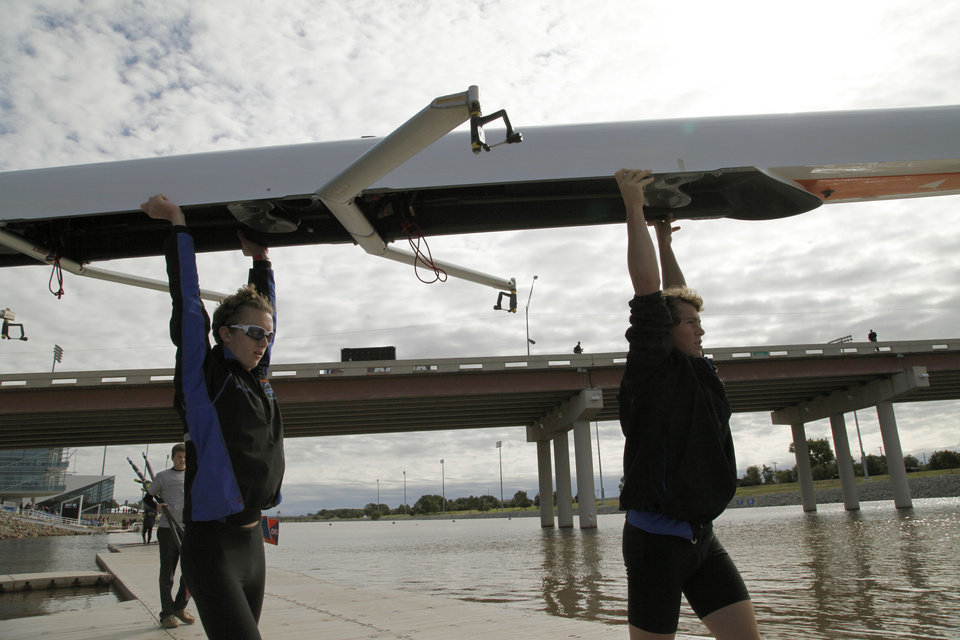 Photo - A team walks their rowing shell to the water during the Oklahoma Regatta Festival on the Oklahoma River in Oklahoma City, OK, Saturday, October 5, 2013,  Photo by Paul Hellstern, The Oklahoman