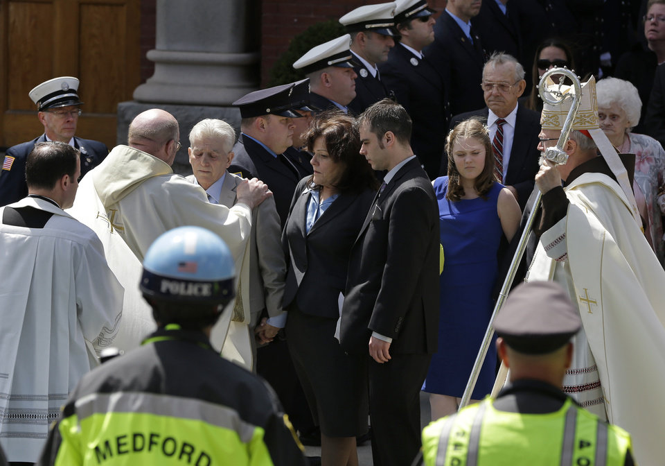Photo - A priest comforts family members of Boston Marathon bomb victim Krystle Campbell after her funeral at St. Joseph's Church in Medford, Mass. Monday, April 22, 2013. At center is her mother, Patty Campbell, and her brother, Billy. At far right is Boston Cardinal Sean O'Malley. (AP Photo/Elise Amendola)