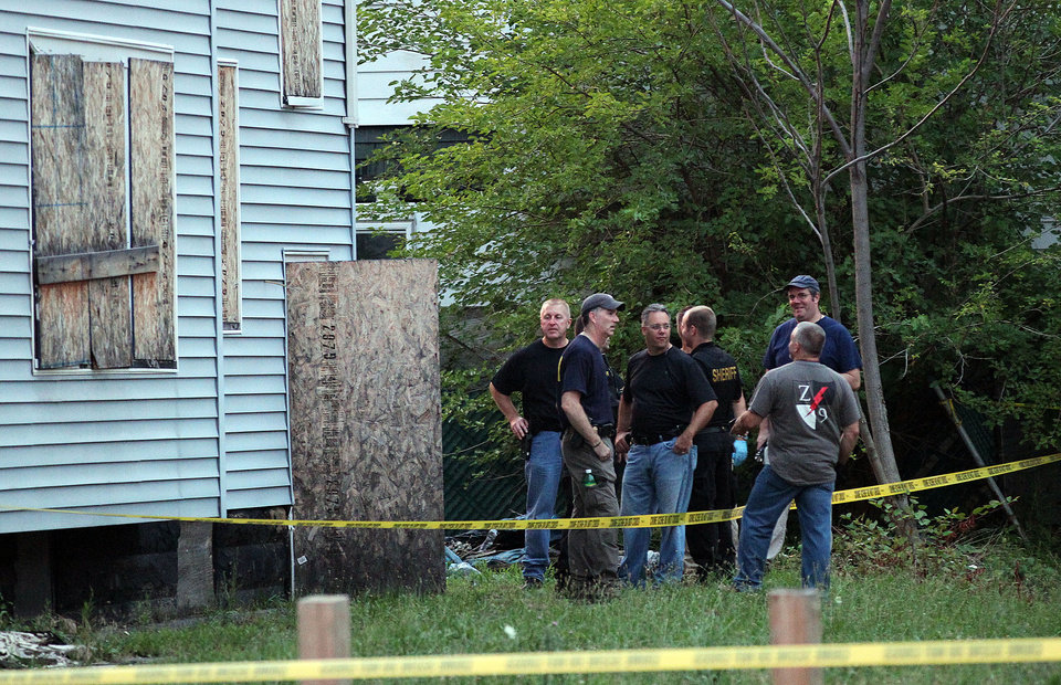 Photo - Law enforcement and FBI stand at the back of a boarded-up home where bodies were found earlier in the day Saturday, July 20, 2013 in East Cleveland, Ohio. Police say three bodies have been found in plastic bags in East Cleveland. Police Commander Mike Cardilli said a woman's body was found Friday in a garage and two other bodies were found Saturday _ one in a backyard and the other in the basement of a vacant house. (AP Photo/The Plain Dealer, Joshua Gunter) MANDATORY CREDIT; NO SALES