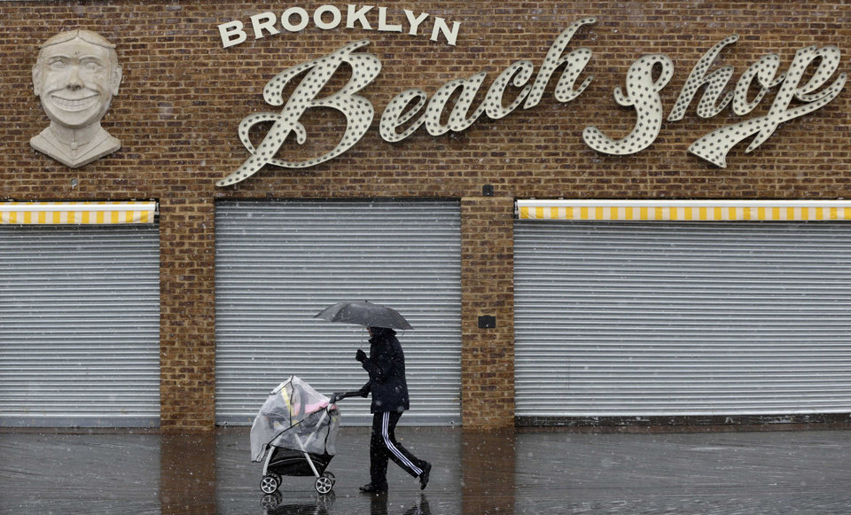 Photo - A pedestrian and a baby try to keep the snow off while walking along the Coney Island boardwalk in New York, Monday, March 25, 2013. A wide-ranging storm is hitting the East Coast after blanketing the Midwest and burying thoughts of springtime weather under a blanket of heavy wet snow and slush, though less snow was predicted to fall as the storm moves eastward. (AP Photo/Seth Wenig)