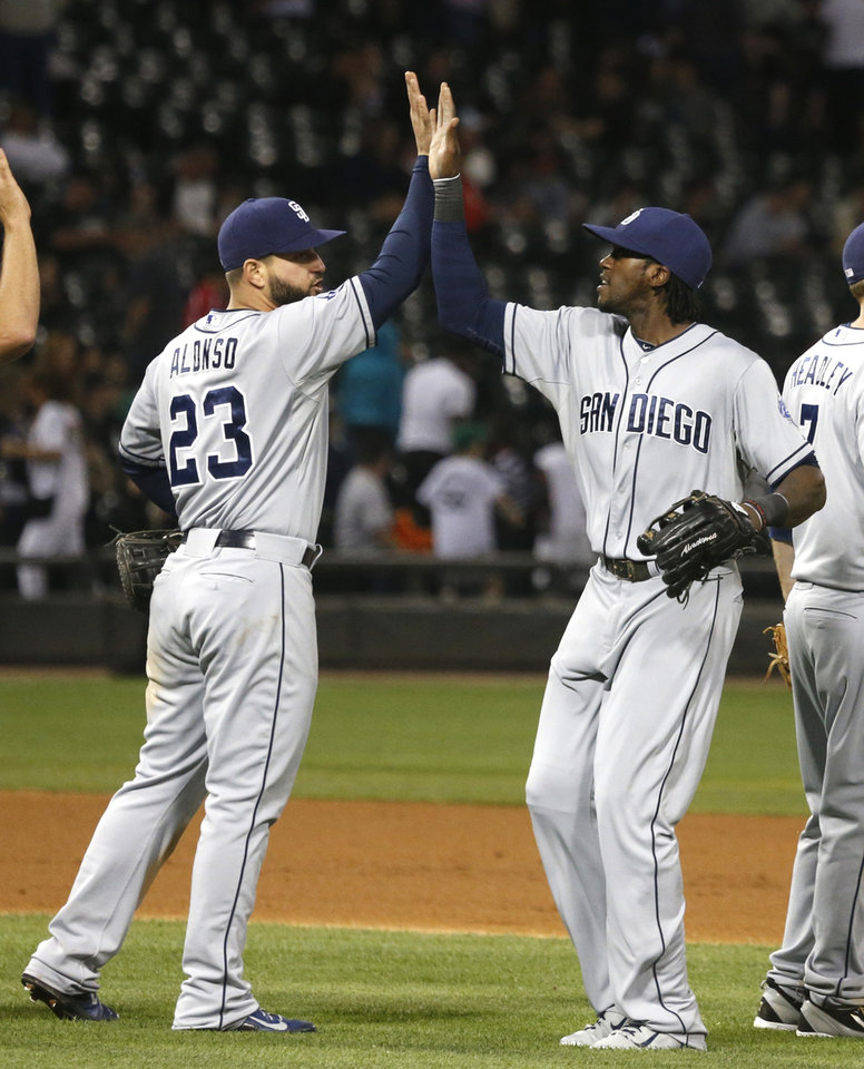 Photo - San Diego Padres first baseman Yonder Alonso (23) and center fielder Cameron Maybin celebrate the Padres' 4-1 win over the Chicago White Sox in an interleague baseball game Friday, May 30, 2014, in Chicago. (AP Photo/Charles Rex Arbogast)