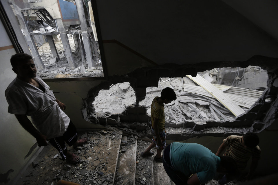 Photo - Palestinians clear the debris as they inspect the damage of the offices of the Hamas movement's Al-Aqsa satellite TV station, in Gaza City, northern Gaza Strip, destroyed by an Israeli strike, Tuesday, July 29, 2014. Early Tuesday, Israel warplanes struck a series of targets in Gaza City, including the top Hamas leader in Gaza, Ismail Haniyeh's house and government offices, while Gaza's border area with Israel was hit by heavy tank shelling. (AP Photo/Lefteris Pitarakis)