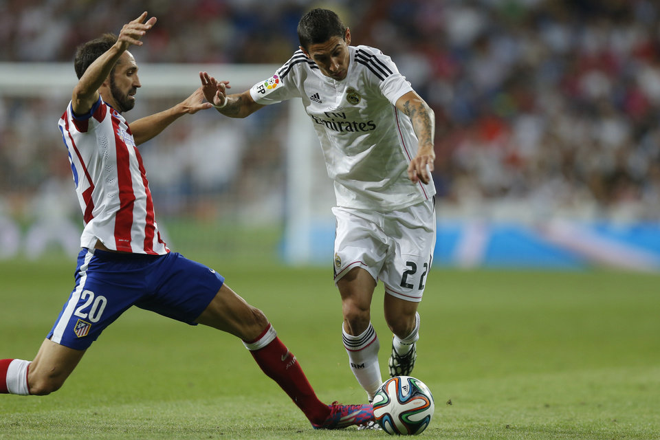 Photo - Real Madrid's Angel Di Maria, right, duels for the ball with Atletico Madrid's Juan Fran during a Spanish Super Cup soccer match at Santiago Bernabeu stadium  in Madrid, Spain, Tuesday, Aug. 19, 2014 . (AP Photo/Daniel Ochoa de Olza)