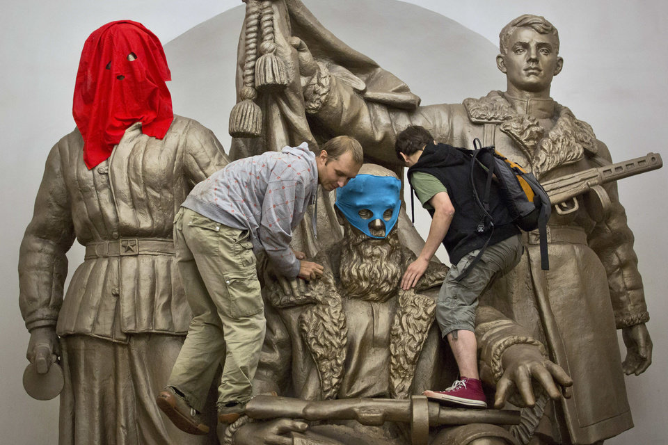 Photo -   Pussy Riot punk group supporters place masks on a monument to WWII heroes to resemble Pussy Riot members, at an underground station in Moscow on Friday, Aug. 17, 2012. Three group members who were jailed in March following a guerrilla performance denouncing President Vladimir Putin in Moscow's main cathedral have unwillingly emerged as vivid — and very different — characters. They await a verdict Friday on charges of hooliganism motivated by religious hatred. (AP Photo/Yevgeny Feldman, Novaya Gazeta)
