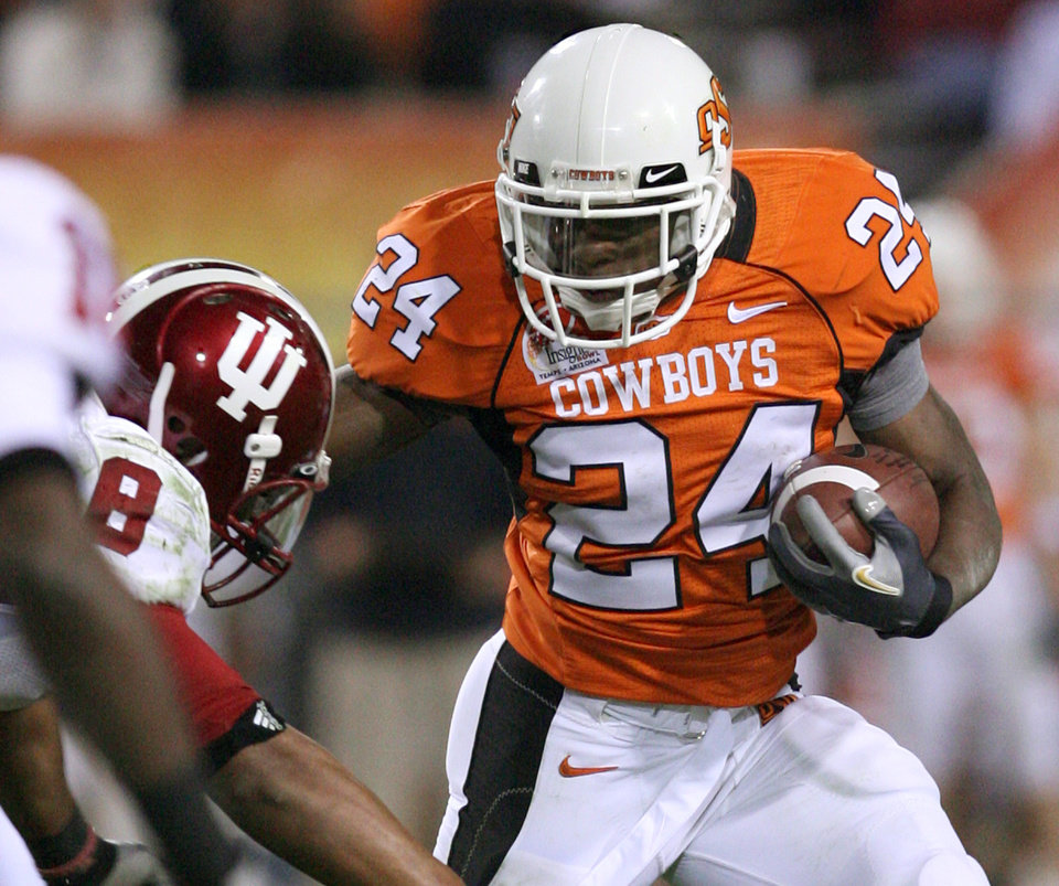 Photo - Oklahoma State University running back Kendall Hunter (24) rushes with the ball against Indiana University's Nick Polk in the second half of the Insight Bowl college football game, Monday, Dec. 31, 2007 in Tempe, Ariz. OSU won 49-33. (AP Photo/Mary Schwalm)  ORG XMIT: PNS117