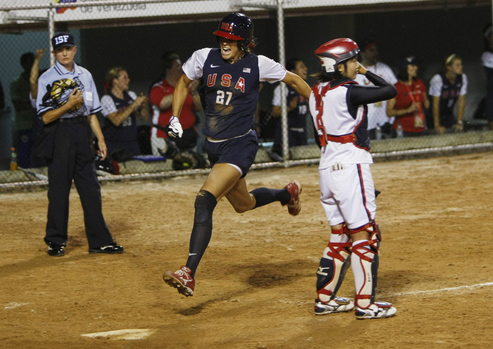 United States' Jennie Finch scores a run as Japan 's catcher Yukiyo Mine looks on during the Womens Softball World Championship game in Caracas, Friday, July 2, 2010. The United States won the gold medal. (AP Photo/Fernando Llano)