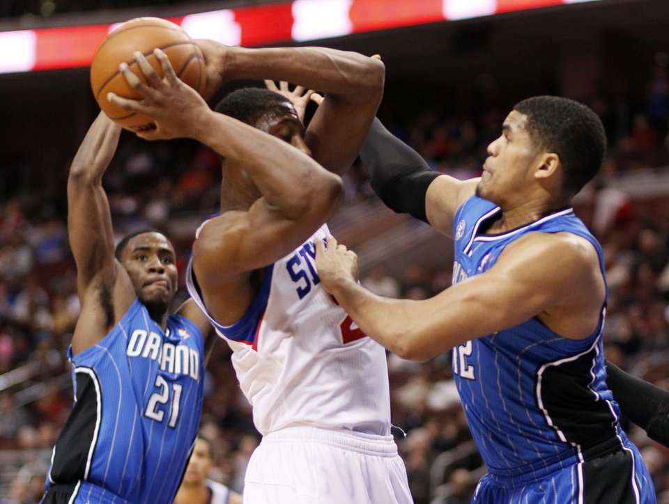 Photo - Philadelphia 76ers' Thaddeus Young, center, is blocked by Orlando Magic's Tobias Harris, right, during the second half of an NBA basketball game on Wednesday, Feb 26, 2014, in Philadelphia. (AP Photo/Tom Mihalek)