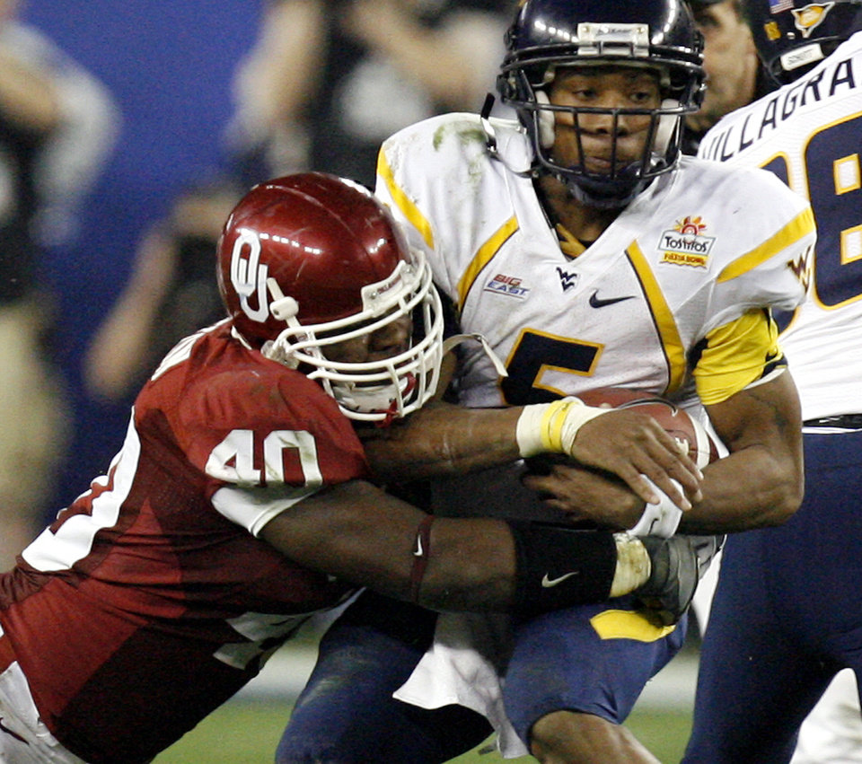 Photo - Oklahoma's Curtis Lofton (40) puts a hit on West Virginia's Patrick White (5) during the first half of the Fiesta Bowl college football game between the University of Oklahoma Sooners (OU) and the West Virginia University Mountaineers (WVU) at The University of Phoenix Stadium on Wednesday, Jan. 2, 2008, in Glendale, Ariz. 