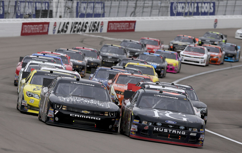Regan Smith (7) and Trevor Bayne (6) lead the pack out of a caution during the NASCAR Nationwide Series auto race, Saturday, March 9, 2013 in Las Vegas. (AP Photo/Julie Jacobson)
