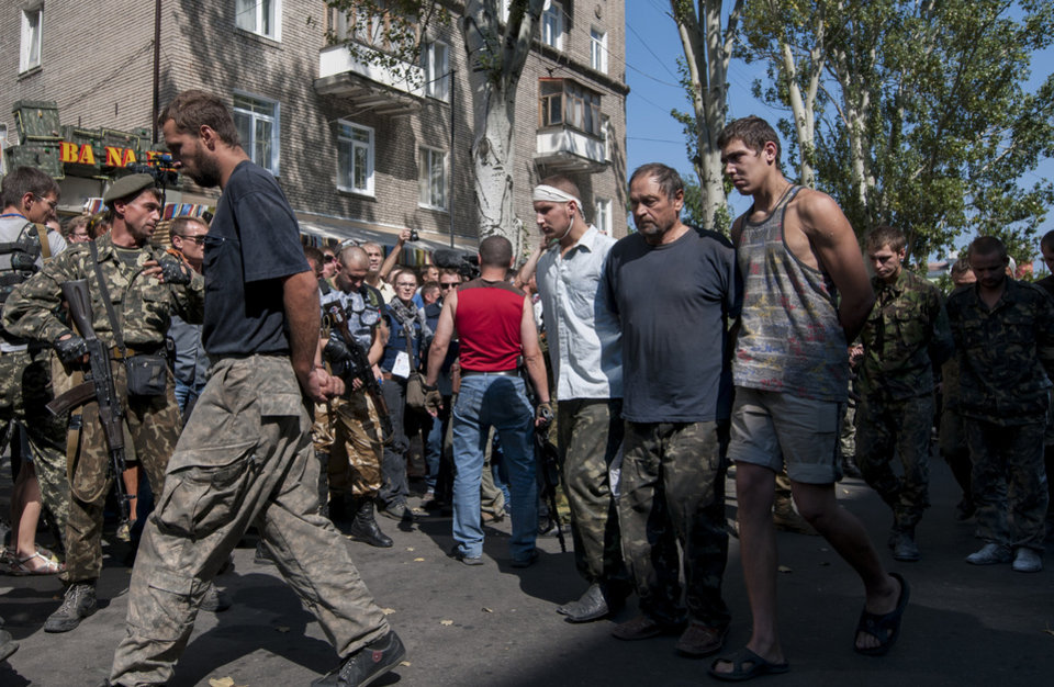 Photo - Pro-Russian rebels escort captured Ukrainian army prisoners in a central square in Donetsk, eastern Ukraine, Sunday, Aug. 24, 2014. Ukraine has retaken control of much of its eastern territory bordering Russia in the last few weeks, but fierce fighting for the rebel-held cities of Donetsk and Luhansk persists. (AP Photo/Antoine E.R. Delaunay)