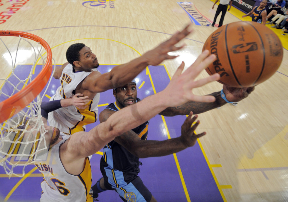 Photo -   Denver Nuggets point guard Ty Lawson, right, puts up a shot as Los Angeles Lakers center Andrew Bynum, upper left, and power forward Pau Gasol of Spain defend during the first half of an NBA first-round playoff basketball game, Sunday, April 29, 2012, in Los Angeles. (AP Photo/Mark J. Terrill)