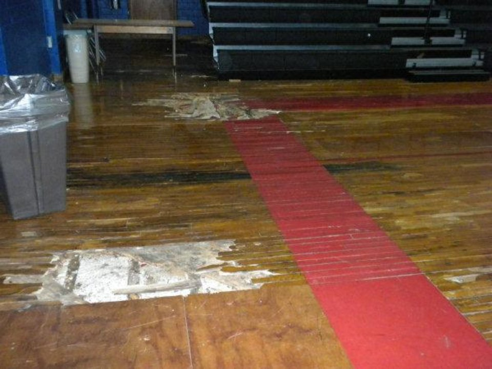 Photo - The damaged gymnasium floor at Taft Middle School, 2901 NW 23, is shown before the busted portions were recently replaced by a member of Mayflower United Church of Christ. Photo provided