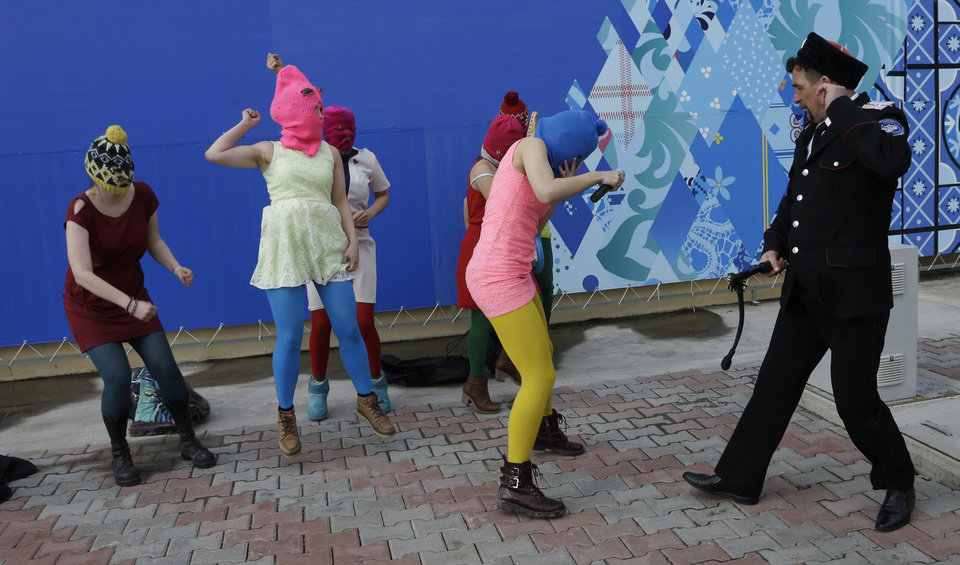 Photo - Nadezhda Tolokonnikova covers her face as she is attacked by a Cossack militiaman while she and fellow members of the punk group Pussy Riot, including Maria Alekhina, second left, in the pink balaclava, stage a protest performance in Sochi, Russia, on Wednesday, Feb. 19, 2014. The group had gathered in a downtown Sochi restaurant, about 30km (21miles) from where the Winter Olympics are being held. They ran out of the restaurant wearing brightly colored clothes and ski masks and were set upon by about a dozen Cossacks, who are used by police authorities in Russia to patrol the streets. (AP Photo/Morry Gash)
