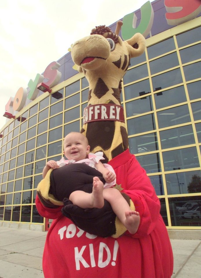 Photo - Geoffrey holds Zoe VonHolt 1yr., outside toys r us.They will hold a safety day this Saturday from 10:00 am to 4:00 pm. They will be inspecting car seats and etc. ( see michelle story for additional info.)