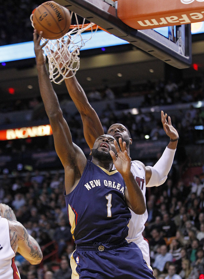 Photo - New Orleans Pelicans' Tyreke Evans (1) goes to the basket against Miami Heat's Dwyane Wade, back, during the first half of an NBA basketball game in Miami, Tuesday, Jan 7, 2014. (AP Photo/Joel Auerbach)
