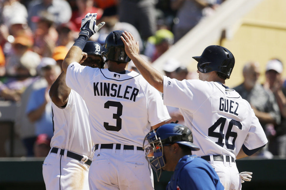 Photo - Detroit Tigers' Ian Kinsler is greeted at home plate by teammates Torii Hunter, left, and Ben Guez after scoring on his three-run home run during the fifth inning of a spring exhibition baseball game against the Toronto Blue Jays in Lakeland, Fla., Tuesday, March 18, 2014. (AP Photo/Carlos Osorio)
