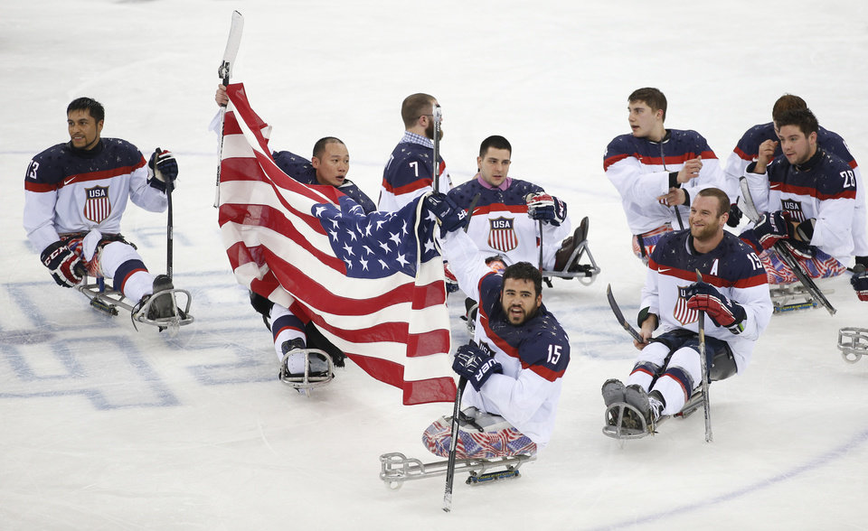 Photo - United States players celebrate as they win the gold medal after their ice sledge hockey match against Russia at the 2014 Winter Paralympics in Sochi, Russia, Saturday, March 15, 2014. United States won 1-0. (AP Photo/Pavel Golovkin)