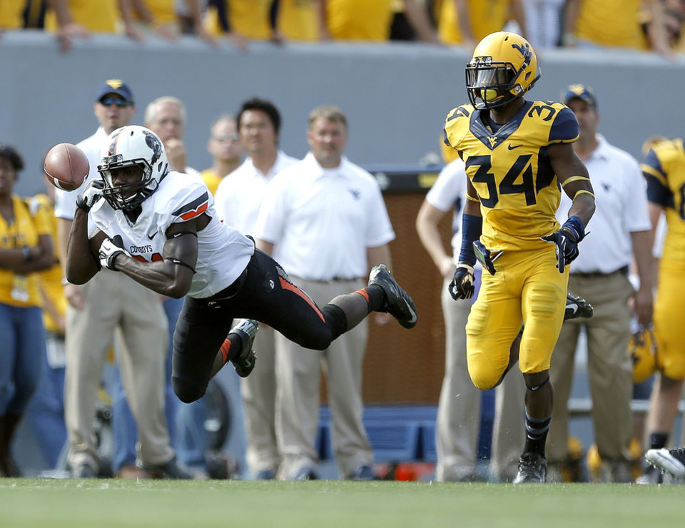Photo - Oklahoma State's Tracy Moore (87) misses a catch in front of West Virginia's Ishmael Banks (34) late in the fourth quarter of a college football game between the Oklahoma State University and West Virginia University on Mountaineer Field at Milan Puskar Stadium in Morgantown, W. Va.,   Saturday, Sept. 28, 2013. Photo by Sarah Phipps, The Oklahoman
