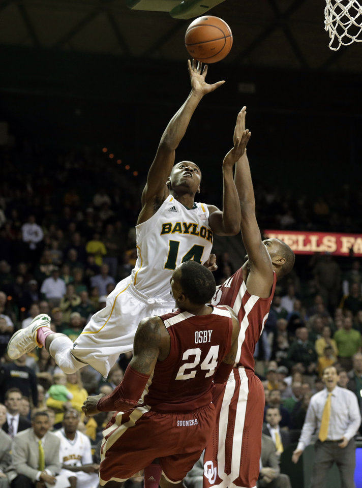Photo - Baylor's Deuce Bello (14) goes up for a shot as Oklahoma's Romero Osby (24) and Amath M'Baye, right, defend during the second half of an NCAA college basketball game Wednesday, Jan. 30, 2013, in Waco, Texas. Bello was charged with an offensive foul on the play. Oklahoma won 74-71. (AP Photo/Tony Gutierrez) ORG XMIT: TXTG112