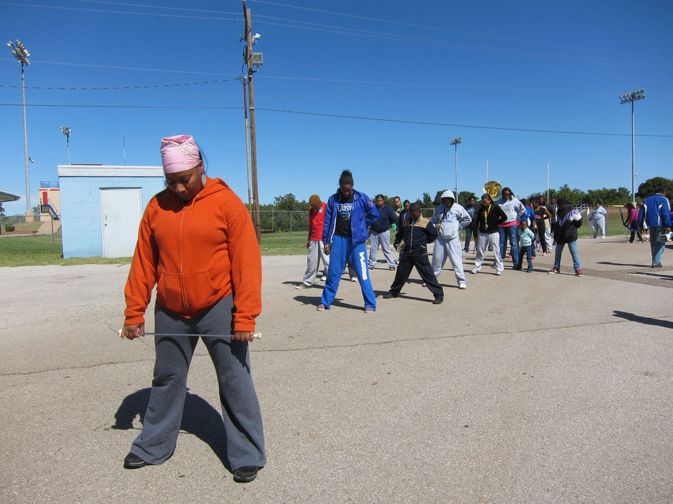 Photo - Class of 1989 graduate Mariechia Hamilton Palmer, 42, practices with the Millwood High School marching band on Saturday (Oct. 5) at the school, 6724 N Martin Luther King Avenue. Palmer was a drum major.  Carla Hinton - The Oklahoman