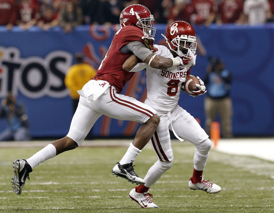 Photo - Oklahoma's Jalen Saunders (8) tries to break free fromAlabama's Eddie Jackson (4) during the NCAA football BCS Sugar Bowl game between the University of Oklahoma Sooners (OU) and the University of Alabama Crimson Tide (UA) at the Superdome in New Orleans, La., Thursday, Jan. 2, 2014. Photo by Sarah Phipps, The Oklahoman