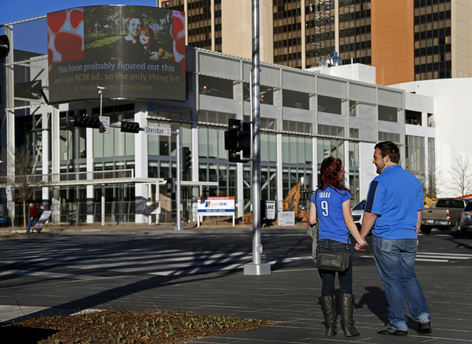 Photo - Ben Edison and his girlfriend Allyson Bond watch a video on the Oklahoman's big screen on the corner of Robinson and Sheridan in Oklahoma City, Saturday, Feb. 14, 2015. Photo by Bryan Terry, The Oklahoman