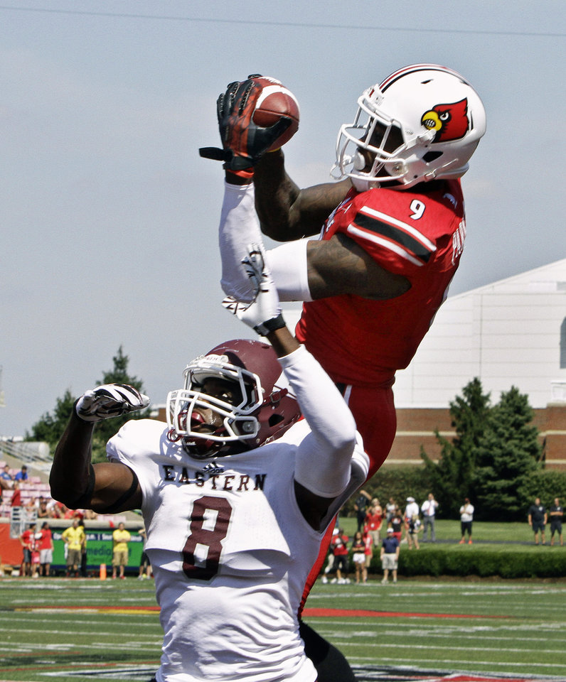 Photo - Louisville wide receiver DeVante Parker (9) makes this 19-yard pass reception in the end zone over Eastern Kentucky defender Johnny Joseph (8) in the first quarter of a NCAA college football game in Louisville, Ky., Saturday, Sept. 7, 2013. (AP Photo/Garry Jones)