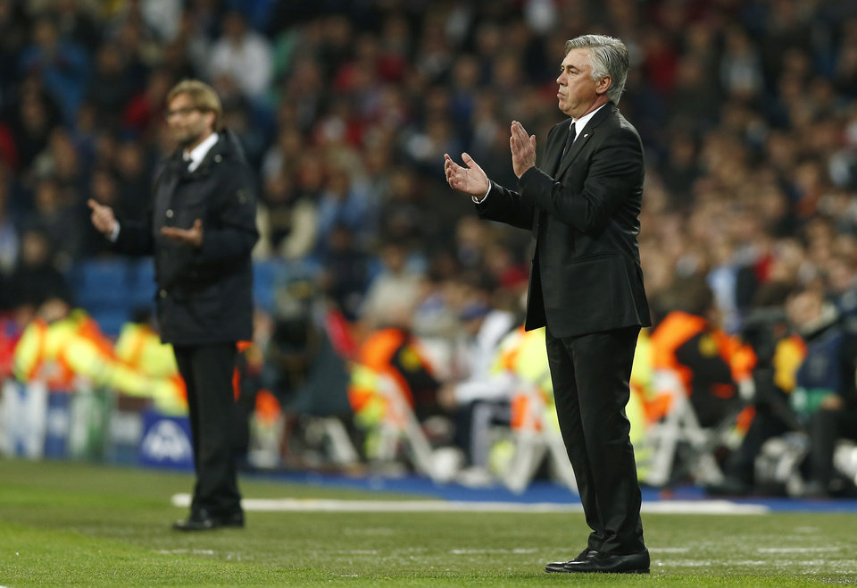 Photo - Dortmund head coach Juergen Klopp, left, and Real's coach Carlo Ancelotti gestures as they stand on the sideline during a Champions League quarterfinal first leg soccer match between Real Madrid and Borussia Dortmund at the Santiago Bernabeu   stadium in Madrid, Spain, Wednesday, April 2, 2014. (AP Photo/Andres Kudacki)