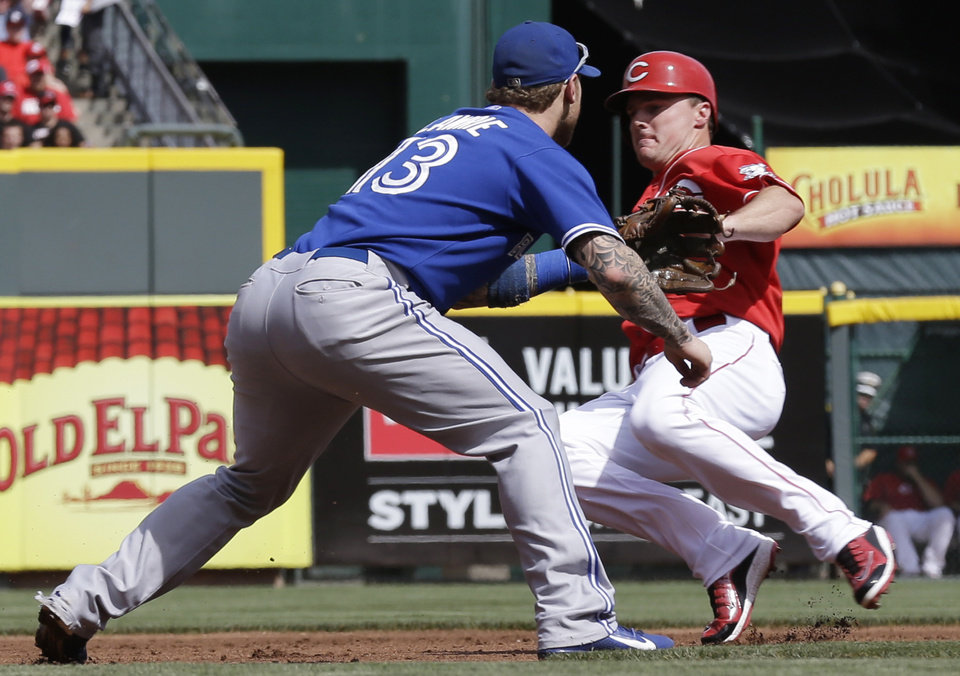 Photo - Cincinnati Reds' Jay Bruce, right, advances to third base as Toronto Blue Jays third baseman Brett Lawrie waits for the throw in the first inning of a baseball game on Saturday, June 21, 2014, in Cincinnati. Bruce advanced to third on a hit by Ryan Ludwick and scored later in the inning on a passed ball by catcher Erik Kratz. (AP Photo/Al Behrman)