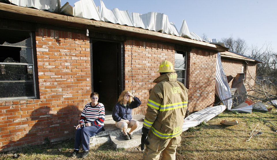 Photo - A Lone Grove firemen talks with Carol McFarland and Lana Hartman about the home on the north side of SH 70 that Lana moved into two days before the tornado struck in Lone Grove, Wednesday, Feb. 11, 2009. BY PAUL B. SOUTHERLAND, THE OKLAHOMAN